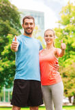 Smiling couple showing thumbs up outdoors Royalty Free Stock Photography