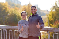 Smiling couple showing thumbs up outdoors Stock Images