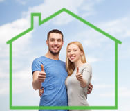 Smiling couple showing thumbs up over green house Stock Photography