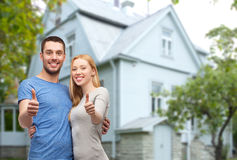 Smiling couple showing thumbs up over house Stock Photos