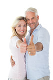 Smiling couple showing thumbs up together Stock Photos