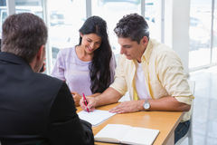 Smiling couple signing a contract Stock Image