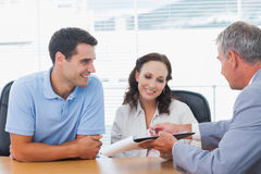 Smiling couple signing contract with real estate agent. In bright office stock photo