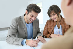 Smiling couple signing contract Royalty Free Stock Images