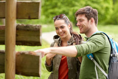 Smiling couple at signpost with backpacks hiking Stock Image