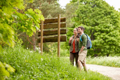 Smiling couple at signpost with backpacks hiking Stock Photo