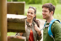 Smiling couple at signpost with backpacks hiking Stock Photography