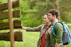 Smiling couple at signpost with backpacks hiking Royalty Free Stock Image