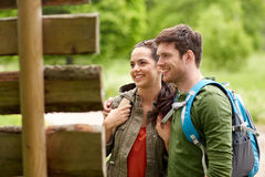 Smiling couple at signpost with backpacks hiking Stock Photos