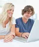 A smiling couple sit together as they surf the internet Royalty Free Stock Images