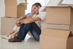 Smiling couple sitting amid boxes in new house Royalty Free Stock Photography