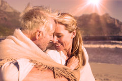 Smiling couple sitting on the beach under blanket Stock Image