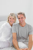 Smiling couple sitting on bed Royalty Free Stock Photo