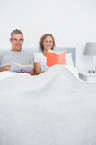 Smiling couple sitting in bed reading books Royalty Free Stock Image