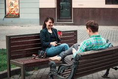 Smiling couple sitting on bench talking to each other drinking coffee stock images