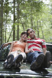 Smiling Couple Sitting On Car Bonnet In Forest Royalty Free Stock Image