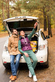 Smiling couple sitting in car trunk Stock Photos