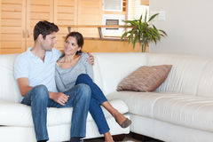 Smiling couple sitting on a couch Stock Images