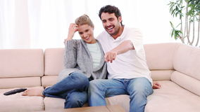 Smiling couple sitting on the couch while watching the television stock video