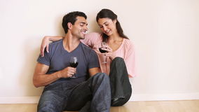 Smiling couple sitting down while clinking their glasses. In an empty room stock video