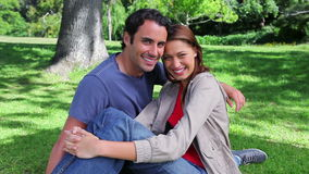 Smiling couple sitting on the grass stock video footage