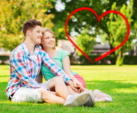 Smiling couple sitting on grass in summer park Stock Images