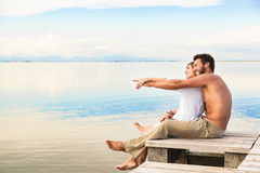Smiling Couple sitting on a jetty and pointing to the horizon Royalty Free Stock Photo