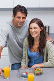 Smiling couple sitting in kitchen Stock Image