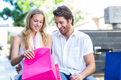 Smiling couple sitting and looking into shopping bags Royalty Free Stock Photos