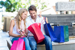 Smiling couple sitting and looking into shopping bags Royalty Free Stock Images