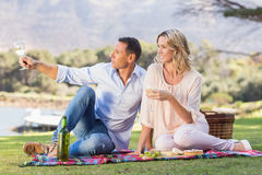 Smiling couple sitting on picnic blanket and enjoying the view Stock Images