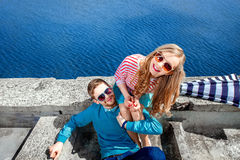 Smiling couple sitting on the pier embracing and smiling on the Stock Images