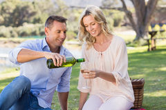 Smiling couple sitting and pouring wine in glass Royalty Free Stock Photography