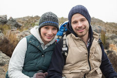 Smiling couple sitting on rock while on a hike Royalty Free Stock Image