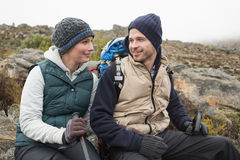 Smiling couple sitting on rock while on a hike Stock Photo