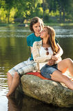 Smiling couple sitting on a rock romantic Stock Photos