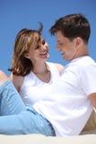 Smiling couple sitting on sand Stock Photo