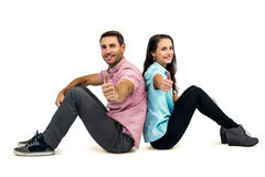Smiling couple sitting showing thumbs up Stock Photo