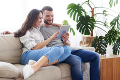 Smiling couple sitting on sofa and surfing in tablet royalty free stock image