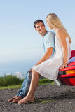 Smiling couple sitting on their cabriolet car hood Royalty Free Stock Image