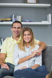 Smiling couple sitting on their couch Stock Image