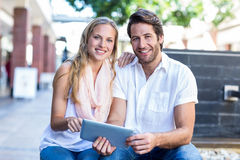 Smiling couple sitting and using tablet computer together Royalty Free Stock Image