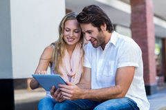 Smiling couple sitting and using tablet computer together Royalty Free Stock Photography