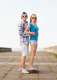 Smiling couple with skateboard outdoors Royalty Free Stock Photos