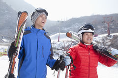 Smiling Couple in Ski Resort Holding Skis Stock Images
