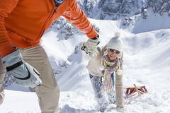 Smiling couple with sled climbing hill with mountain in background royalty free stock images