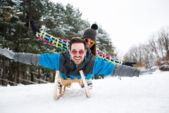 Smiling couple sledding together on sleigh. On beautiful snow day Royalty Free Stock Photos