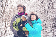 Smiling couple with the small dog, in funny winter hats. Standing in the forest, among snow covered trees and enjoying life. Quiet winter day Stock Image