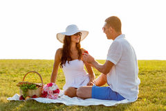 Smiling couple with small red gift box on picnic Royalty Free Stock Image