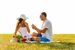 Smiling couple with small red gift box on picnic Stock Photos